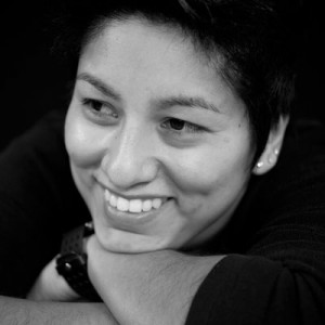 A black and white headshot of a smiling Angie Herrera.